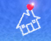 Red heart shape clothespin cloud house. In blue sky Stock Image