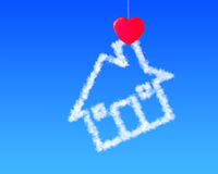 Red heart shape clothespin holding cloud house. In blue sky Stock Photo
