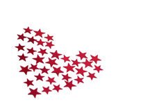 Red heart shape of confetti. A red heart shape made out of red star shaped confetti on an isolated white background Royalty Free Stock Photography