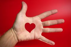 Red heart shape drawed on a male human hand. Red backround Stock Photography