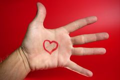 Red heart shape drawed on a male human hand. Red backround Royalty Free Stock Image