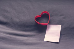 Red heart shape and empty note paper on bed. Royalty Free Stock Image