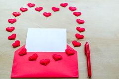 Red heart shape with envelope and pen on wooden background Royalty Free Stock Images
