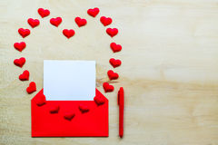 Red heart shape with envelope and pen on wooden background Stock Photo