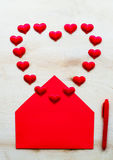 Red heart shape with envelope and pen on wooden background Royalty Free Stock Image