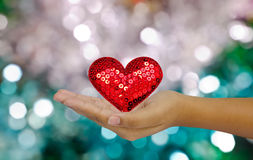 Red heart shape in hand over colorful lights bokeh Royalty Free Stock Images