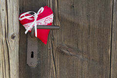 Red heart shape hanging on door handle or a wooden Background, c Royalty Free Stock Images