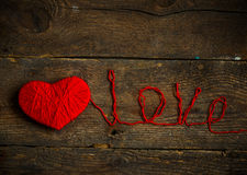 Red heart shape with an inscription love made from wool on old s Royalty Free Stock Photography