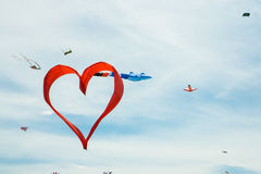 Red heart shape kite is flying in blue sky Royalty Free Stock Images