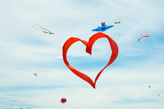 Red heart shape kite is flying in blue sky Stock Image