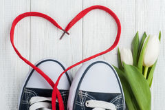 Red heart shape from laces and blue sneakers Stock Image