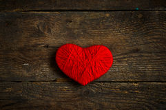 Red heart shape made from wool on old shabby wooden background Stock Images