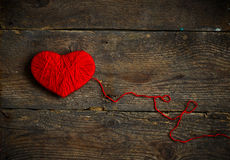 Red heart shape made from wool on old shabby wooden background Stock Image