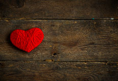 Red heart shape made from wool on old shabby wooden background Royalty Free Stock Photography
