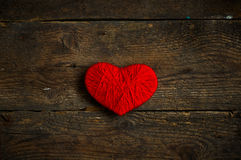 Red heart shape made from wool on old shabby wooden background Royalty Free Stock Images