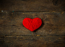 Red heart shape made from wool on old shabby wooden background Royalty Free Stock Image