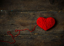 Red heart shape made from wool on old shabby wooden background Stock Photos
