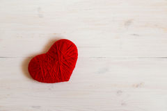 Red heart shape made from wool on white wooden background Stock Image