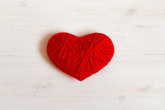Red heart shape made from wool on white wooden background Stock Photography