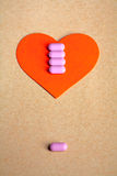 Red heart shape over craft paper with row of small pink pill on and copy space on the top. Heart health concept. Royalty Free Stock Photos