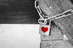 Red heart shape over rustic padlock on wooden bridge over black Stock Images