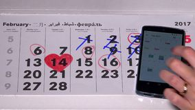 Red heart shape on paper calendar and woman hand touching smart phone. VILNIUS, LITHUANIA - NOVEMBER 30, 2016: Red heart shape on paper calendar on february stock video footage