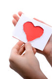Red heart shape paper in hand. Hand holding a red heart shape paper cut out of paper on a white background Stock Image