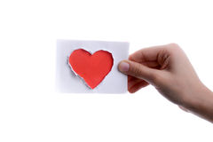 Red heart shape paper in hand. Hand holding a red heart shape paper cut out of paper on a white background Royalty Free Stock Photography