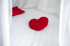 Red heart shape pillow on white bed sheet stock photo