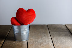 Red Heart Shape pillows in Metal bucket on wooden background Stock Photography