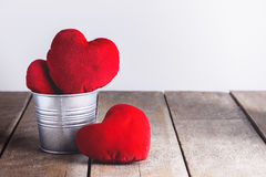 Red Heart Shape pillows in Metal bucket on wooden background Royalty Free Stock Photography