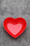 Red heart shape plate. On grunge background Royalty Free Stock Photography