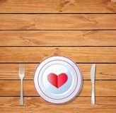 Red heart shape on a plate on wooden table surface. Romantic love dinner. Red heart shape on a plate with knife and fork on wooden table surface. Vector Royalty Free Stock Images