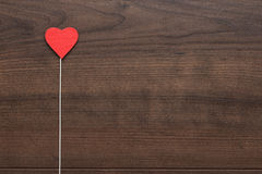 Red heart shape on stick. Over wooden background Stock Photos