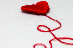 Red heart shape symbol made from wool  on white Stock Photos