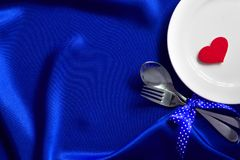 Red heart shape with White empty plate with fork and spoon on bl Royalty Free Stock Images