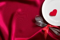 Red heart shape with White empty plate with fork and spoon on re Stock Photo