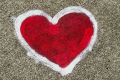 Red heart shape with white outline painted sprayed on massive concrete wall. Creative simple concept symbolic for love, romance, passion, couple, valentines royalty free stock image