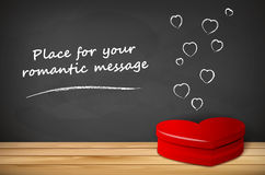 Red heart shape on wooden tabletop and chalkboard Royalty Free Stock Image
