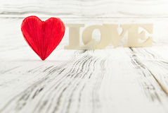 Red heart shaped and in the background wooden letters forming word love Stock Image