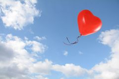 Red heart shaped balloon flies into the blue sky with clouds, love concept, copy space. Red heart shaped balloon flies into the blue sky with clouds, love royalty free stock photo