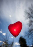 Red heart-shaped balloon in sky Stock Photography