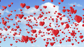 Red heart shaped balloons in the blue sky with clouds. Royalty Free Stock Photos