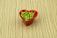 Red heart-shaped bowl, keep fresh peas Royalty Free Stock Photo