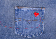 Red heart shaped button with needle and red thread on denim fabr Stock Photo