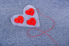 Red heart shaped buttons with needle and red thread Royalty Free Stock Images