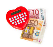 Red heart shaped calculator with euro banknotes. Royalty Free Stock Photos