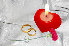 Red candle with engagement rings Royalty Free Stock Photography