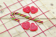 Red heart shaped candles and a candy cane Royalty Free Stock Photo