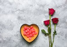 Red heart shaped candy bowl with rose. Red roses placed in a bowl of red heart-shaped candy on a gray-white surface, with a copy space for the Valentines Day stock photo